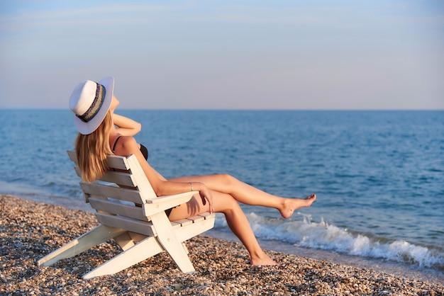 Ein mädchen mit hut sitzt auf einem stuhl am meer. Premium Fotos