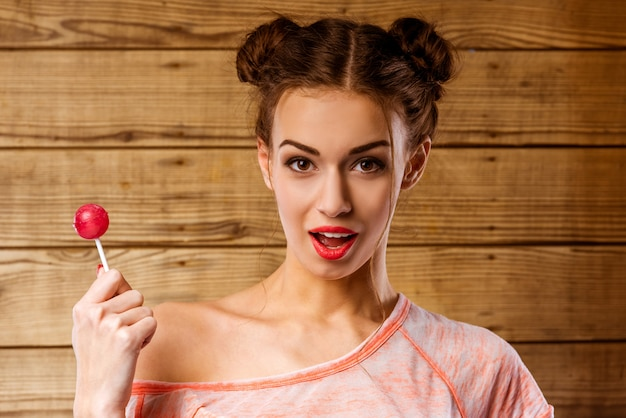 Ein mädchen mit offenem mund steht mit einem lutscher. Premium Fotos