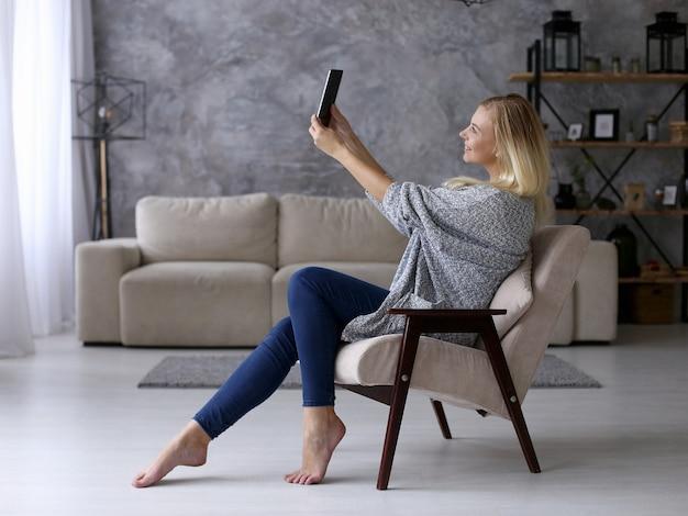 Ein mädchen sitzt auf einem stuhl und fotografiert auf einem tablet. arbeiten sie bequem von zu hause aus per video. copyspace. Premium Fotos