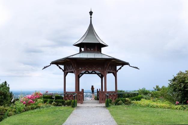 Ein mädchen steht auf der aussichtsplattform im pavillon und fotografiert die schöne aussicht. Premium Fotos