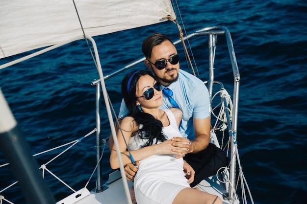 Ein mädchen und ein mann mit asiatischem aussehen sitzen auf dem deck der yacht und umarmen sich. ein paar hände berühren sich. Premium Fotos