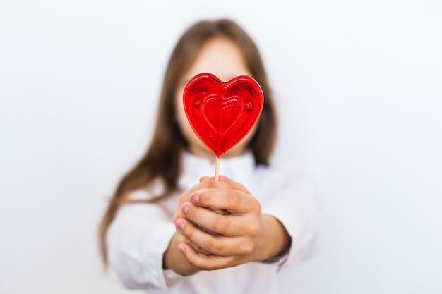 Ein mädchen von europäischem aussehen auf einem weißen hintergrund hält einen herzförmigen lutscher in ihrer hand, liebe, geschenk, familie, valentinstag Premium Fotos