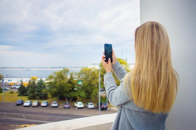 Ein mädchenreisender nimmt am telefon einen überblick über eine großstadt mit blick auf den fluss. Premium Fotos