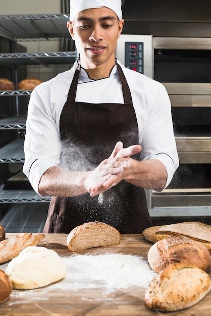 Ein männlicher bäcker, der das mehl mit den händen auf geknetetem teig abwischt Kostenlose Fotos