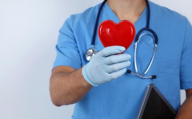 Ein männlicher doktor, der ein herz hält Premium Fotos