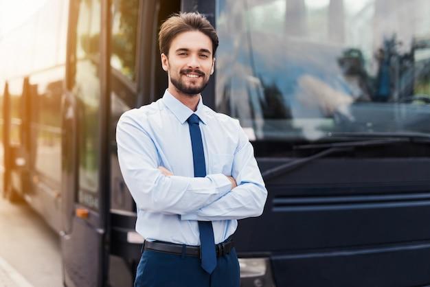 Ein männlicher fahrer, der gegen einen schwarzen touristenbus lächelt und aufwirft Premium Fotos