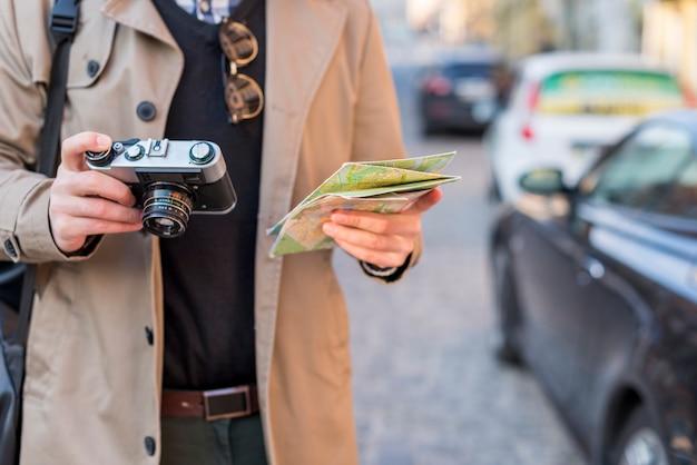 Ein männlicher reisender, der in der hand karten- und weinlesekamera hält Kostenlose Fotos