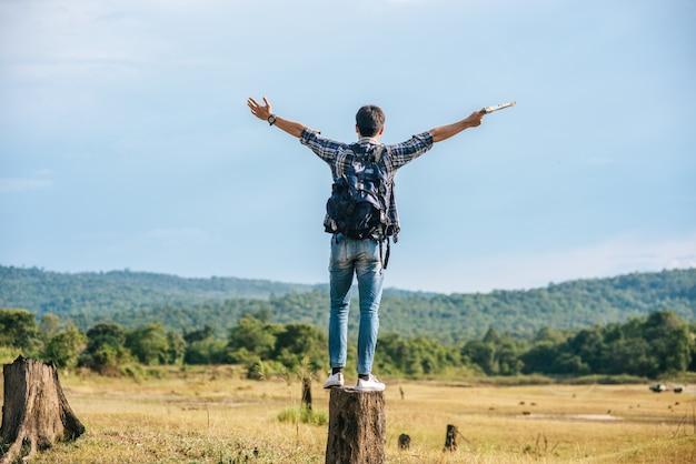Ein männlicher reisender mit einem rucksack, der eine karte trägt und auf einem baumstumpf steht Kostenlose Fotos