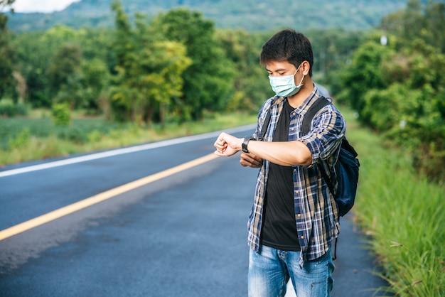 Ein männlicher reisender mit einer umhängetasche und blick auf seine uhr. Kostenlose Fotos