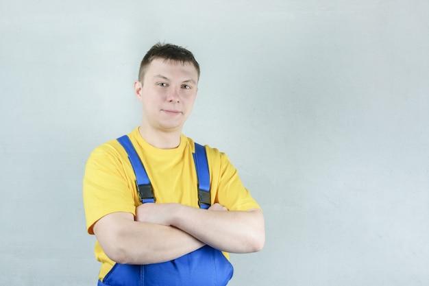 Ein männlicher schlosser in einem blauen overall und einem gelben t-shirt gegen eine graue wand. Premium Fotos