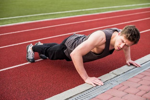 Ein männlicher sportler, der liegestütz auf roter rennstrecke tut Kostenlose Fotos