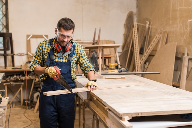 Ein männlicher tischler, der die planke mit handsäge in der werkstatt schneidet Kostenlose Fotos