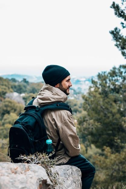 Ein männlicher wanderer, der auf felsen mit seinem rucksack betrachtet ansicht sitzt Kostenlose Fotos