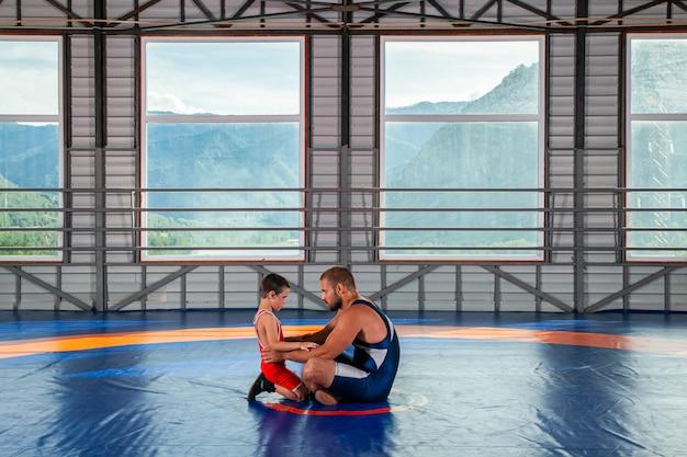 Ein männlicher wrestler-trainer unterrichtet die grundlagen des wrestlings Premium Fotos