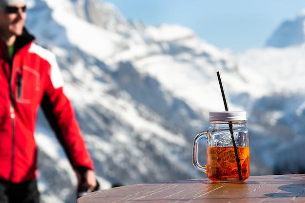 Ein mann auf dem hintergrund der berge geht zu dem tisch, auf dem ein becher aperol steht. Premium Fotos