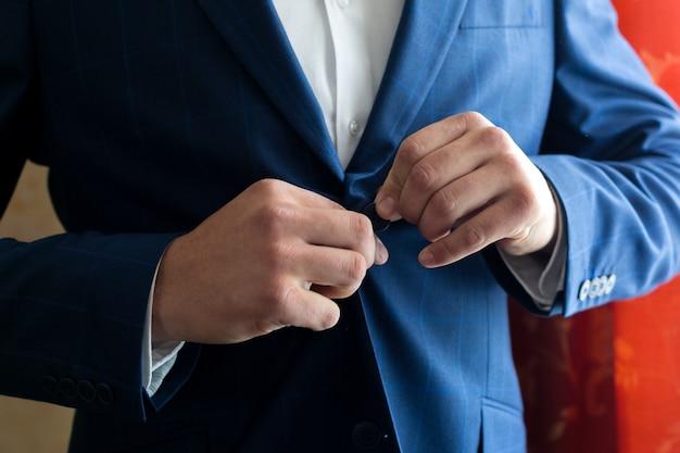 Ein mann befestigt einen knopf seiner jacke auf seinem bauch Premium Fotos