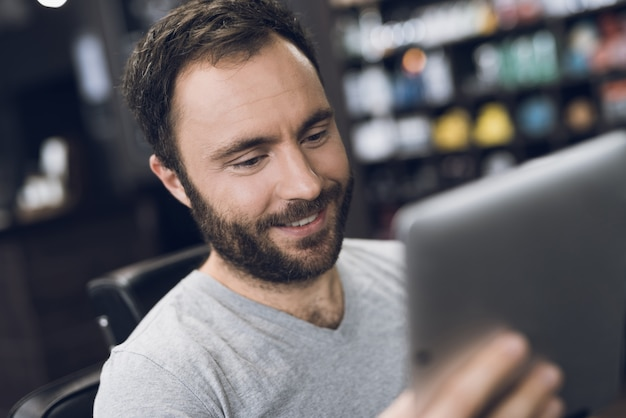 Ein mann betrachtet tablette im friseursessel im friseursalon des mannes. Premium Fotos