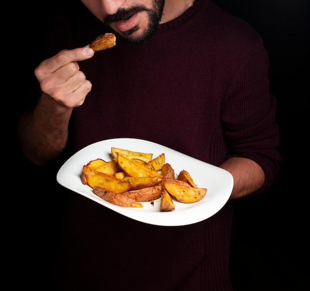Ein mann, der bratkartoffeln von der weißen platte schmeckt Kostenlose Fotos