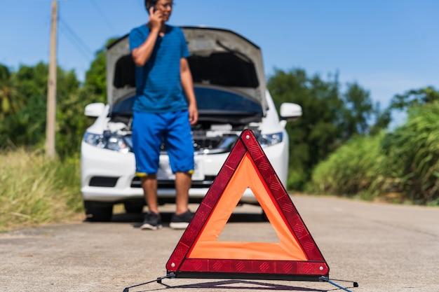 Ein mann, der ein telefon verwendet, während er ein problemauto und ein warnzeichen des roten dreiecks auf der straße hat Premium Fotos