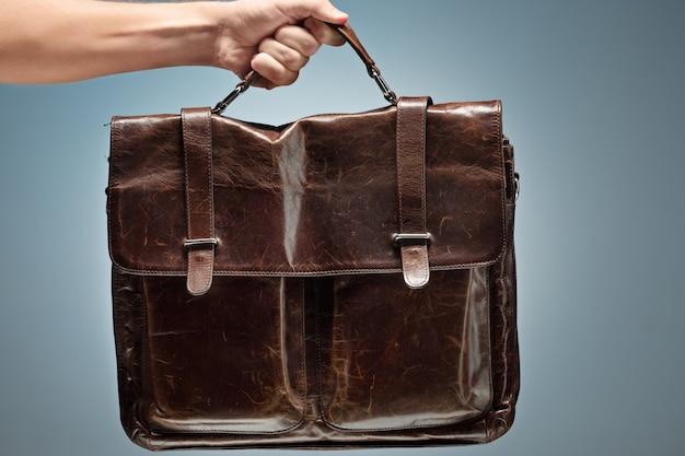 Ein mann, der eine braune lederreisetasche hält Kostenlose Fotos