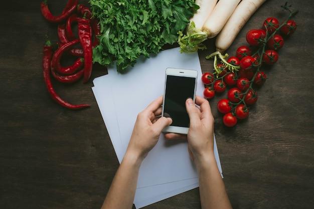 Ein mann, der einen smartphone in seinen händen auf dem küchentisch auf einem hintergrund mit frischgemüse hält. flach liegen Premium Fotos