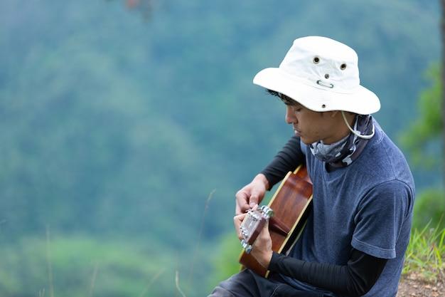 Ein mann, der glücklich sitzt und allein im wald gitarre spielt. Kostenlose Fotos