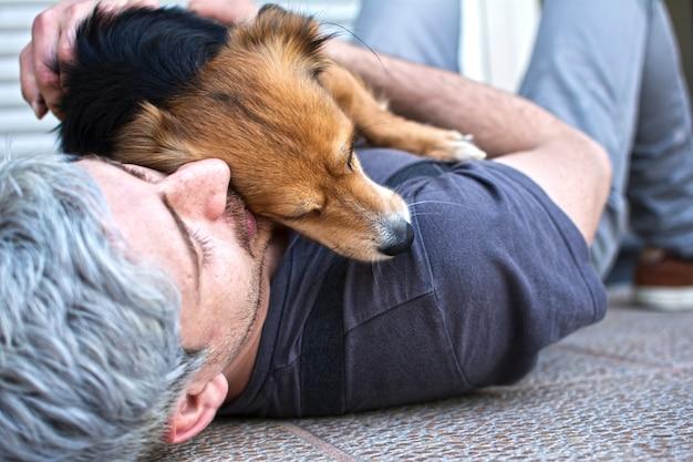 Ein mann, der liegt und seinen hund umarmt, der ihn auf seiner brust liegen hat. Premium Fotos