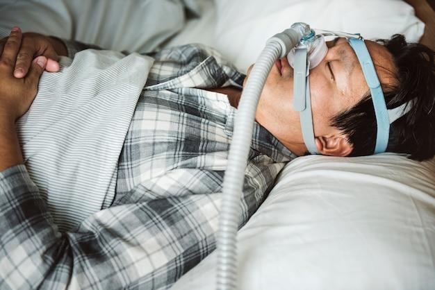 Ein mann, der mit einem schnarchenden kinnriemen schläft Premium Fotos