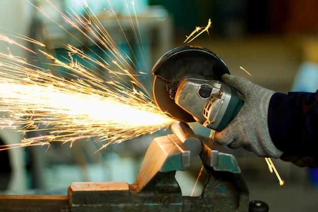 Ein mann, der mit handwerkzeugen arbeitet. hände und funken nahaufnahme. Premium Fotos