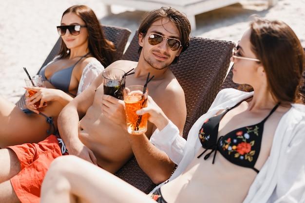 Ein mann, der mit mädchen am strand flirtet Premium Fotos