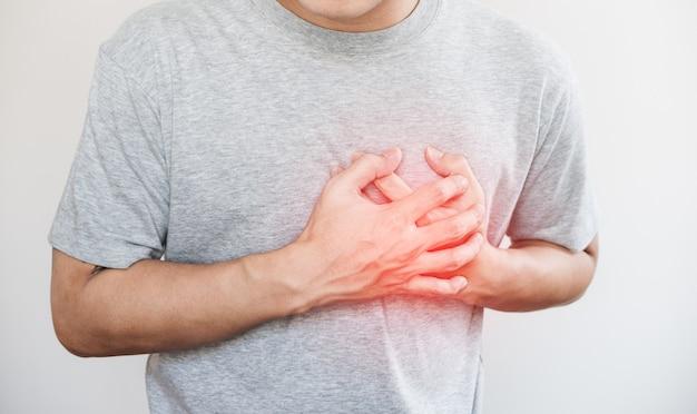 Ein mann, der sein herz, mit rotem höhepunkt des herzinfarkts und anderes herzkrankheitskonzept berührt Premium Fotos