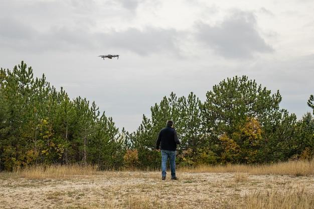 Ein mann geht mit seiner drohne an einem wolkigen herbsttag in einem kiefernwald spazieren Premium Fotos