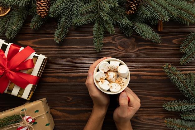 Ein mann hält ein heißes weihnachtsgetränk mit marshmallows und zimt in den händen Premium Fotos