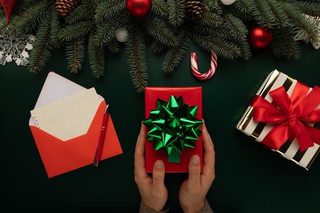 Ein mann hält ein weihnachtsgeschenk in den händen Premium Fotos
