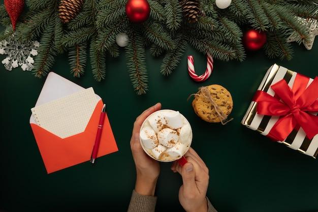 Ein mann hält eine tasse heiße schokolade mit marshmallows in den händen Premium Fotos