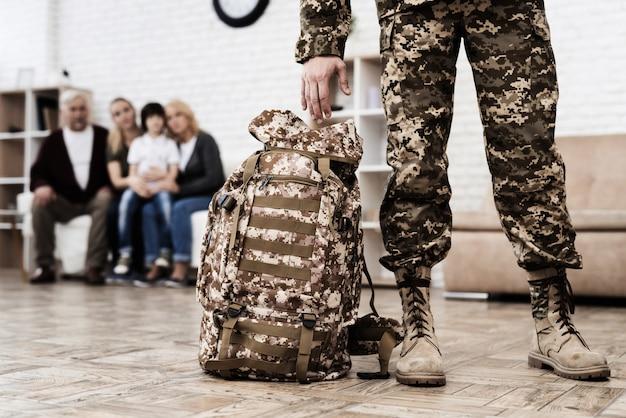 Ein mann hält einen rucksack und zieht in den krieg. Premium Fotos