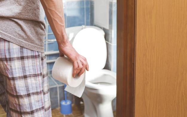 Ein mann hält toilettenpapier. das konzept von durchfall. hämorrhoiden. Premium Fotos