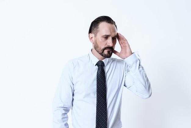 Ein mann hat kopfschmerzen. er hält seine hände auf dem kopf. Premium Fotos