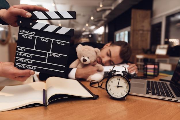 Ein mann im business-anzug schläft am arbeitsplatz. Premium Fotos