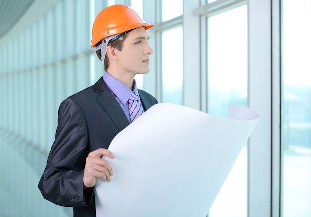 Ein mann in anzug und helm betrachtet einen bauplan. Premium Fotos