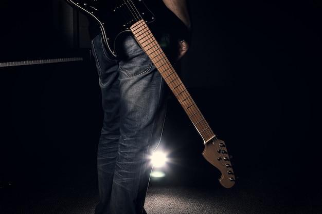 Ein mann in den jeans, die seine e-gitarre auf schwarzem hintergrund halten Premium Fotos