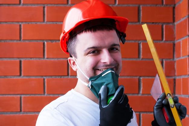 Ein mann in einem schutzhelm trägt ein beatmungsgerät vor dem hintergrund einer roten backsteinmauer. Premium Fotos