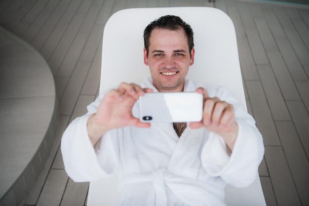 Ein mann in einem weißen bademantel liegt auf einem liegestuhl am pool und schaut in das neue teure handy Premium Fotos