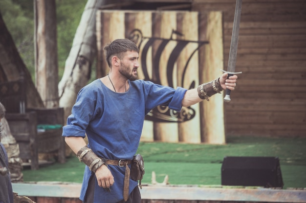 Ein mann in einem wikinger-kostüm nimmt ein schwert in die hand Premium Fotos