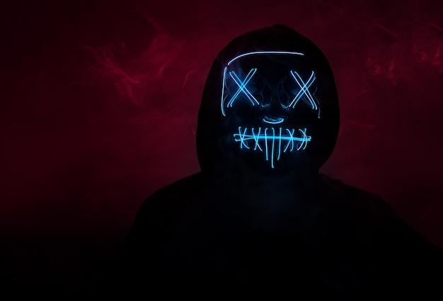 Ein mann in einer gruseligen neon leuchtenden maske und einer kapuze an einer dunklen wand mit rauch. horror- und halloween-konzept Premium Fotos