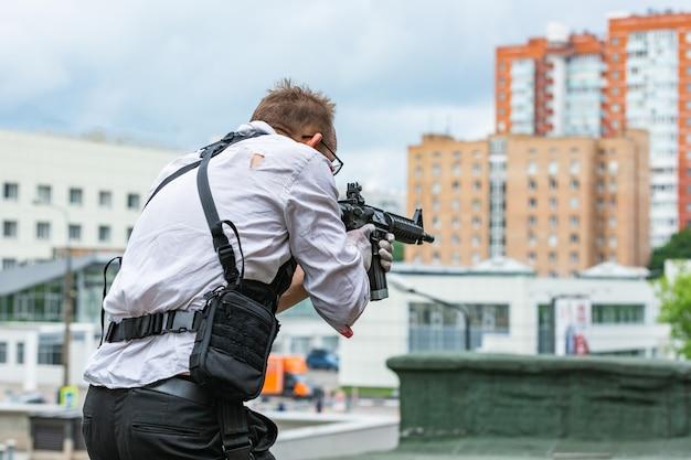Ein mann in einer kugelsicheren weste und einem hemd im blut verfolgt ein opfer mit einer waffe. action-filmstil Premium Fotos