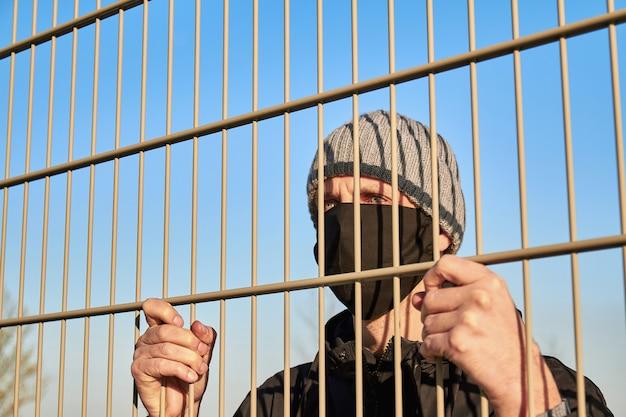 Ein mann in einer schwarzen schutzmaske in der nähe des metallzauns. quarantäne. coronavirus-konzept. ein mann mit schutzmaske. Premium Fotos