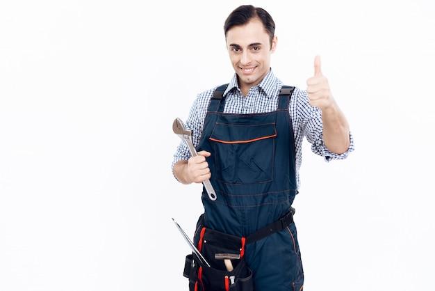 Ein mann in uniform hält einen verstellbaren schraubenschlüssel. Premium Fotos