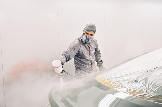 Ein mann malt ein auto Premium Fotos