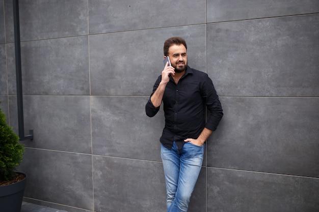 Ein mann mit bart geht und spricht telefonisch Premium Fotos